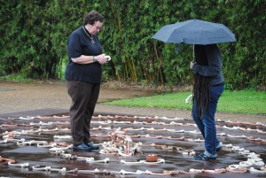 Participants place ceramic bones in the center of the labyrinth. Photo Credit: Alison Pruitt